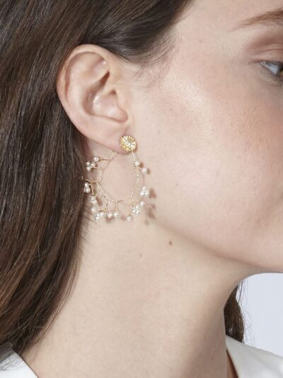Pendientes Alejandría. El hilo dorado cuenta con ensartaciones de perlas. El modelo está coronado por una margarita de plata con baño de oro con una circonita central.