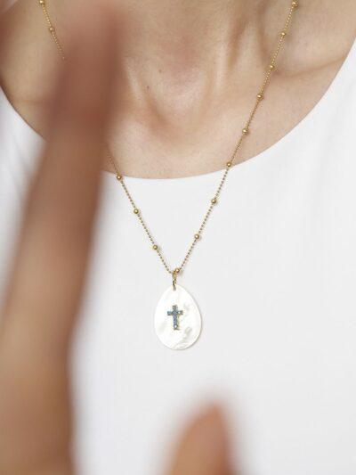 Colgante Cleopatra. Colgante en forma de lágrima de nácar blanca y turquesa en forma de cruz. Cadena de plata de ley de 925 y baño de oro de 18 quilates.