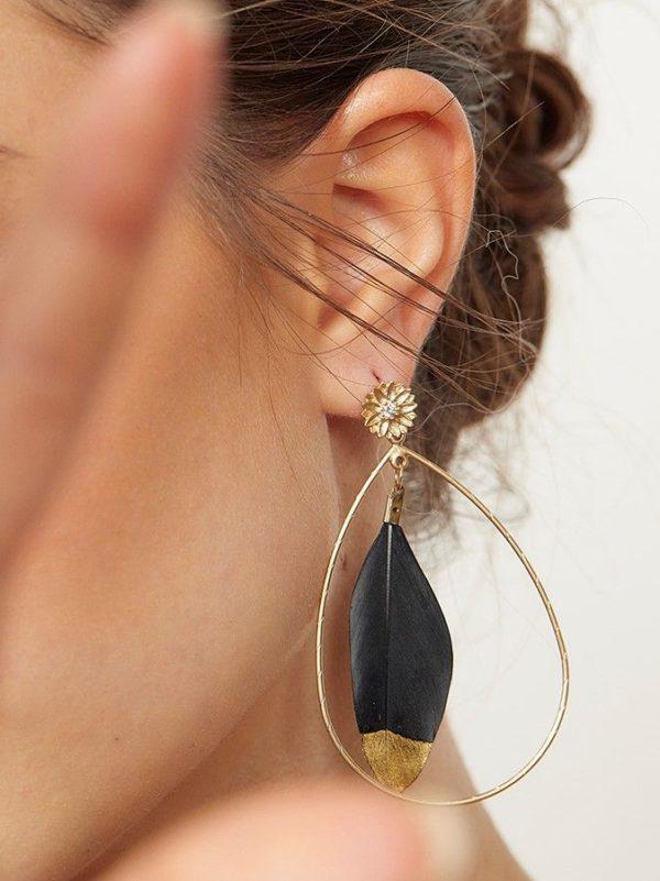 Pendiente Luma Negro Pendiente en forma de aro con pluma negra en la parte central y cierre de tornillo en forma de flor con circonita.