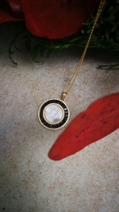 Medalla de virgen de forma circular con circonitas negras en el contorno y virgen labrada en nácar. También las tenemos con circonitas azules.