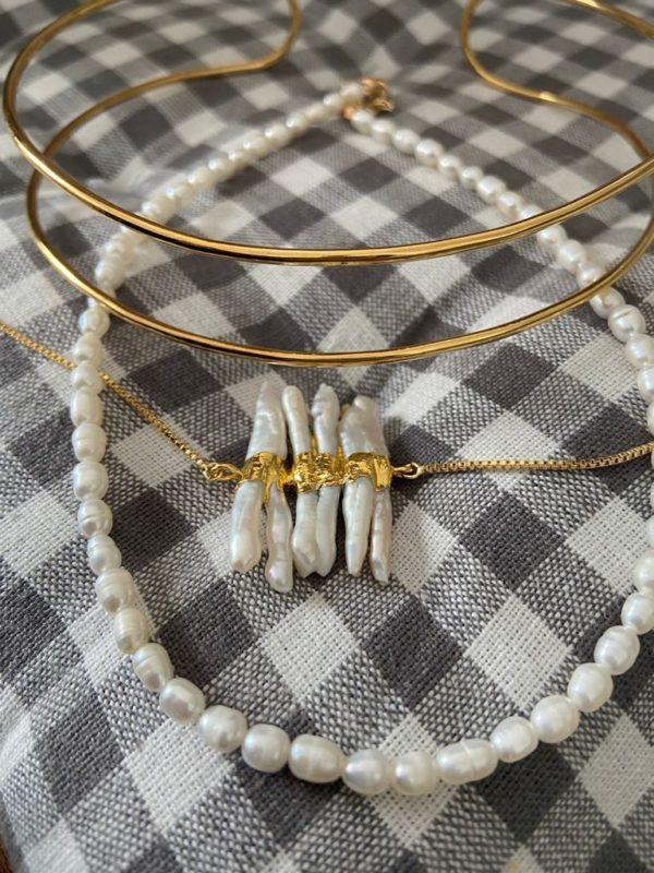Choker de piedras blancas de nácar entrelazadas con metal con baño de oro dorado . Trepille