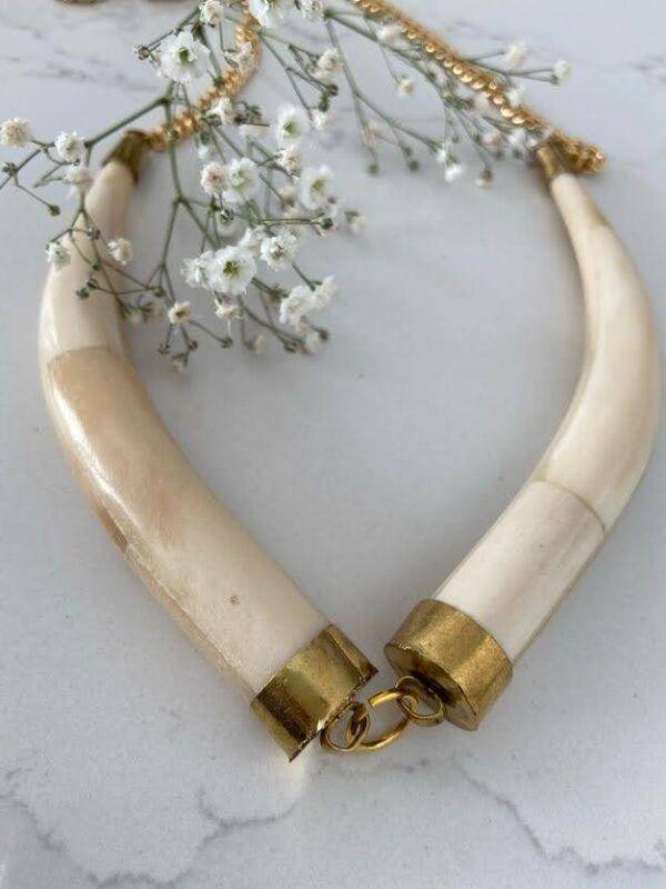 Colgante de doble cuerno realizado en hueso con bordes dorados enlazado s por los extremos. Trepille