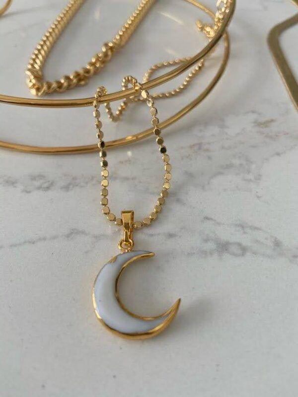 Colgante en forma de luna de hueso rematada en dorado con cadena labrada . Dimensiones 3*3 cm.
