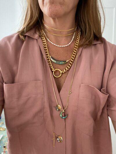 Colgante de doble cuerno madre perla realizado en piedra natural, con cadena de plata con bolitas y baño de oro de 1 micra.